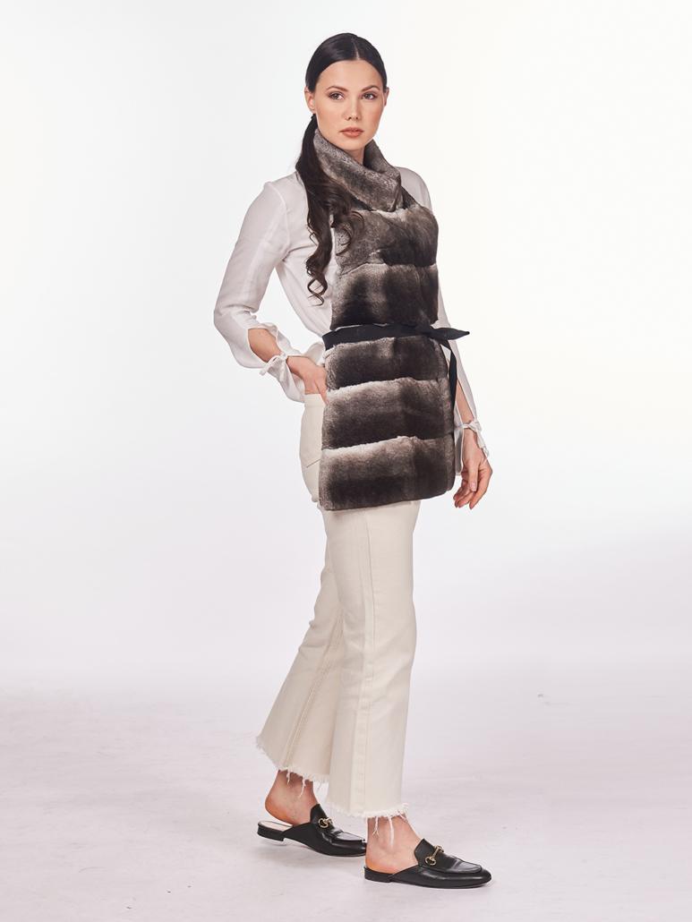 gilet in pelliccia di cincillà e rex con cintura nera aperto sulla schiena, pantaloni bianchi, camicia bianca e mocassini neri